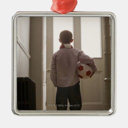 Muchacho en salón con el balón de fútbol ornamento para arbol de navidad