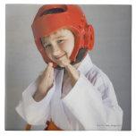 Muchacho en sombrero sparring que lleva uniforme d azulejos ceramicos