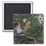 Muchacho hispánico, 8, en silla de ruedas con el b imanes de nevera