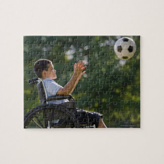 Muchacho hispánico, 8, en silla de ruedas con el b puzzles con fotos