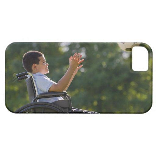 Muchacho hispánico, 8, en silla de ruedas con el funda para iPhone SE/5/5s