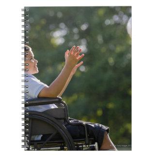 Muchacho hispánico, 8, en silla de ruedas con el libro de apuntes con espiral
