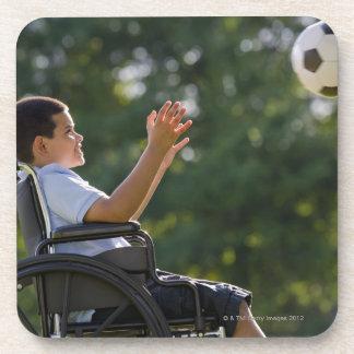 Muchacho hispánico, 8, en silla de ruedas con el posavasos