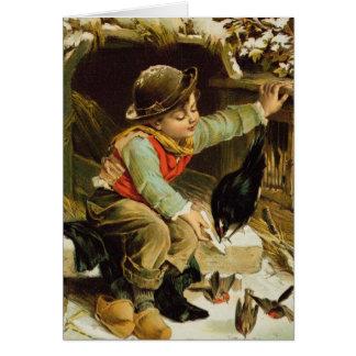Muchacho joven con los pájaros en la nieve felicitación