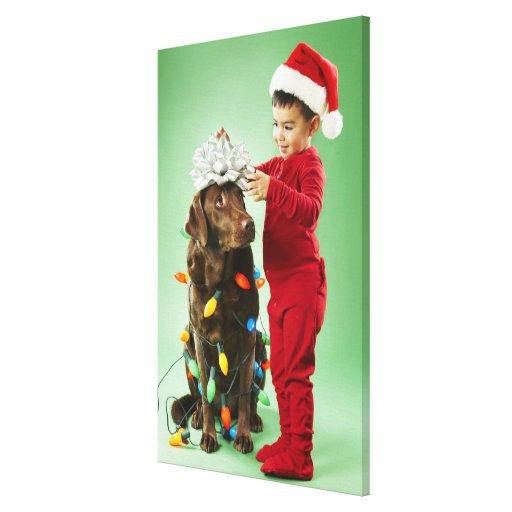 Muchacho joven que envuelve luces de navidad alred lona estirada galerías