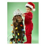 Muchacho joven que envuelve luces de navidad alred postal