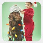 Muchacho joven que envuelve luces de navidad calcomanía cuadradas personalizada