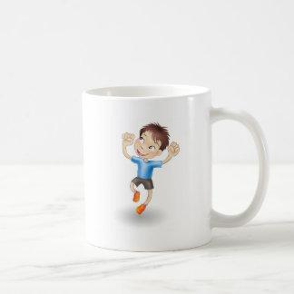 Muchacho joven que salta para la alegría tazas de café