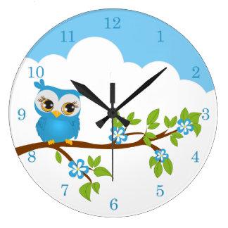 Muchacho lindo del búho en los relojes de una pare