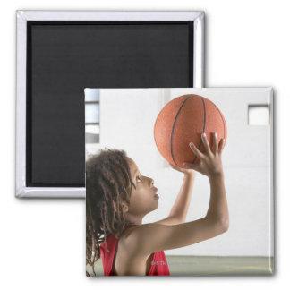 Muchacho que apunta un tiro con un baloncesto en imán cuadrado