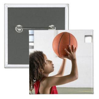 Muchacho que apunta un tiro con un baloncesto en pin cuadrado