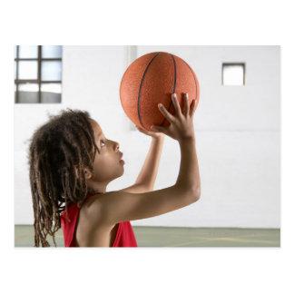 Muchacho que apunta un tiro con un baloncesto en postal