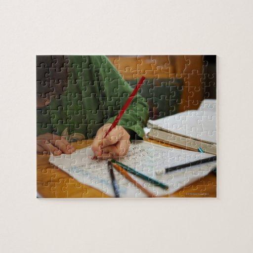 Muchacho que concentra en la preparación de la mat puzzles