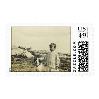Muchacho que hace una pausa su perro en la playa sello