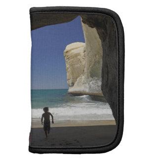 Muchacho que juega en la cueva del mar, playa del  planificadores