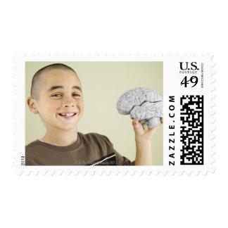 Muchacho que lleva a cabo el modelo del cerebro sellos