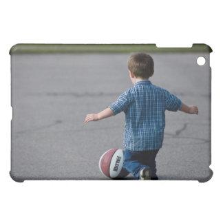 Muchacho que persigue baloncesto al aire libre