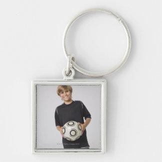 Muchacho que sostiene el balón de fútbol, sonriend llavero