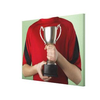 Muchacho que sostiene el trofeo impresión en lona estirada