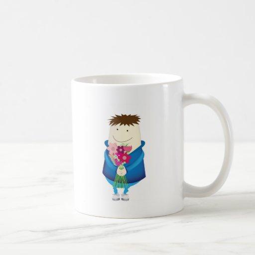 muchacho que sostiene las flores taza de café