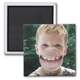 muchacho rubio detrás de la sonrisa de la lupa imán cuadrado