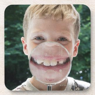 muchacho rubio detrás de la sonrisa de la lupa posavasos de bebida