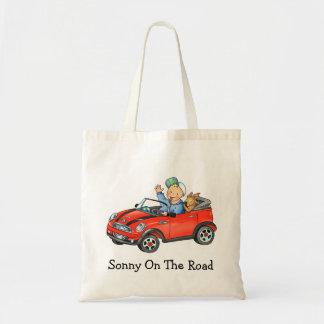 Muchacho y perro en bolso rojo del coche del jugue bolsas