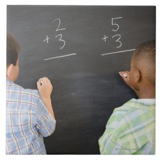 Muchachos que solucionan los problemas de matemáti azulejo cuadrado grande