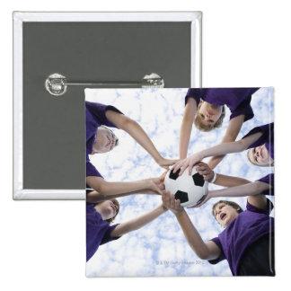 Muchachos que sostienen el balón de fútbol en grup pin cuadrado
