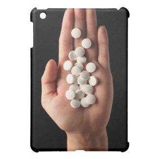 Muchas píldoras blancas en la palma de una persona