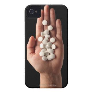 Muchas píldoras blancas en la palma de una persona carcasa para iPhone 4