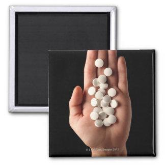 Muchas píldoras blancas en la palma de una persona imán cuadrado