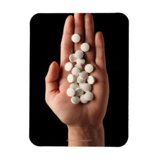 Muchas píldoras blancas en la palma de una persona imán rectangular