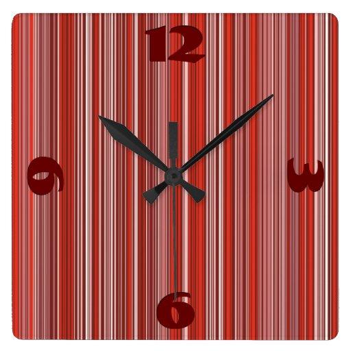 Muchas tiras multicolores en el modelo rojo reloj de pared