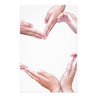 Muchos brazos de chicas construyen el corazón en papelería