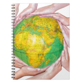 Muchos brazos de niños con las manos que sostienen note book