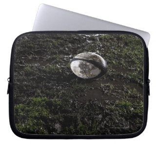 Muddy rugby ball sitting on a chewed up grass laptop computer sleeves