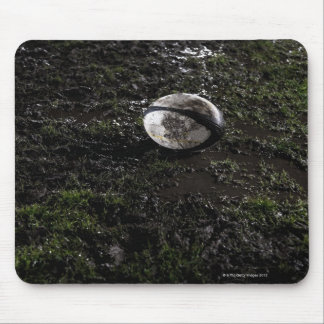 Muddy rugby ball sitting on a chewed up grass mouse pad