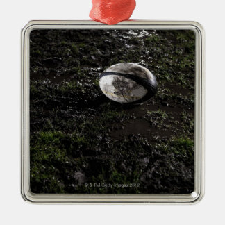 Muddy rugby ball sitting on a chewed up grass square metal christmas ornament