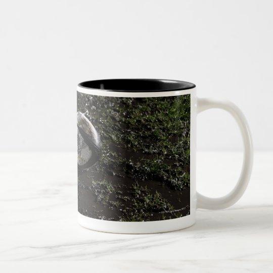 Muddy rugby ball sitting on a chewed up grass Two-Tone coffee mug