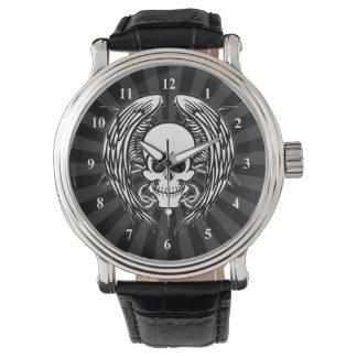 Mueca del cráneo y de las alas del tatuaje con relojes de pulsera