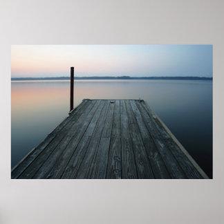 Muelle sobre el agua tranquila en el amanecer póster
