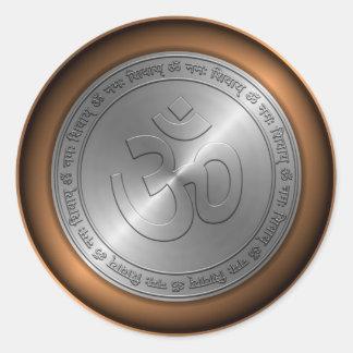 Muestra de OM grabada en relieve en moneda Etiqueta Redonda