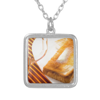 Mug of tea and hot toast with butter silver plated necklace