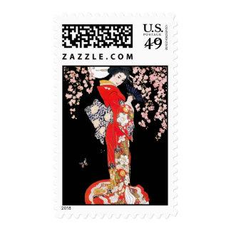 Mujer asiática con noche de la flor de cerezo franqueo