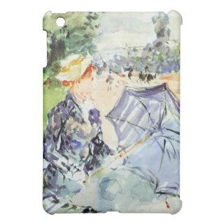 Mujer con el parasol que se sienta en el parque po