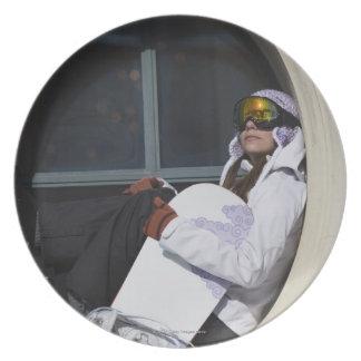 Mujer con la snowboard que se sienta en ventana plato para fiesta