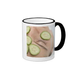 Mujer con las rebanadas de pepino fresco en su car tazas de café