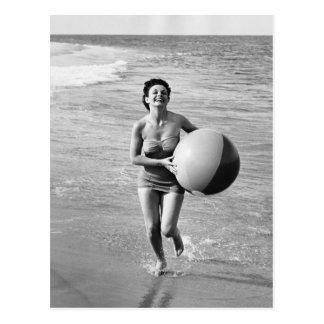 Mujer con una pelota de playa tarjeta postal