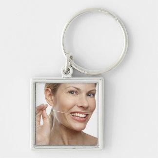 Mujer contra los dientes flossing del fondo llavero cuadrado plateado